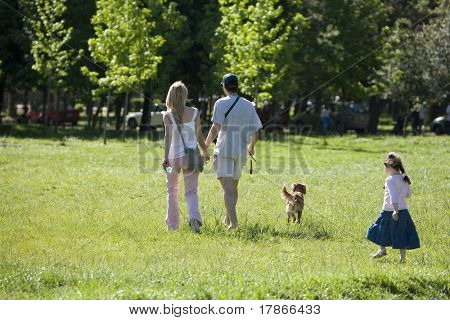Family and dog enjoys Sunday afternoon in park