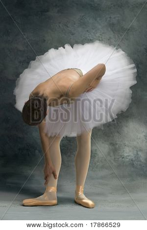 Ballerina bends his body because an ankle pain