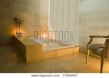 View of a  restroom with a  bubble-bath and candles.