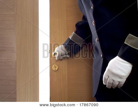 Bellboy opening a door in a hotel