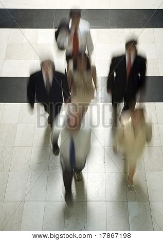 Business people going to work walking through a marble corridor