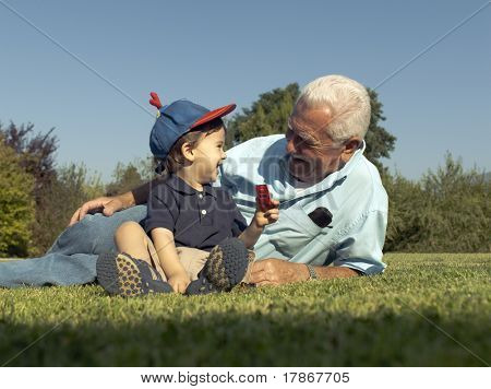 Grandfather and grandson smiling over the grass