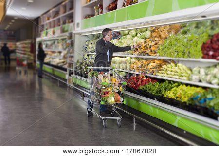 Mann Handy-Anrufe beim pflücken Gemüse in einem Supermarkt. alle erkennbaren Logos und