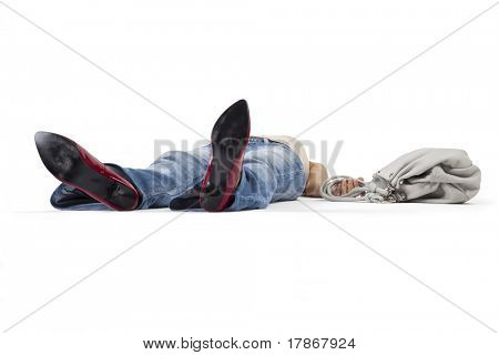 Woman in a faint lying on the floor holding a bag.