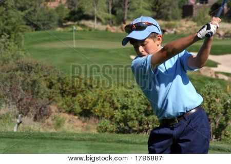 Young Male About To Tee Off On Short Hole With Flag Visible, Focus On Golfer