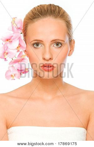 Young beautiful woman with pink orchids in her hair isolated on white