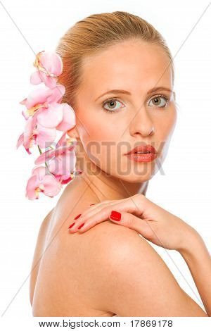 Young beautiful woman with pink orchids in hair holding hand on shoulder isolated on white
