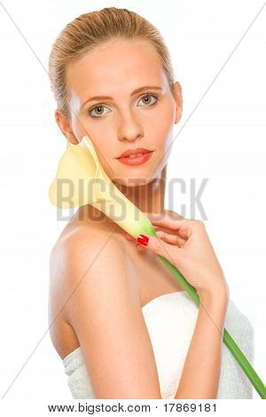 Beautiful young woman holding yellow calla lily in hand isolated on white