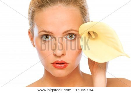 Beautiful young woman with yellow calla lily near face isolated on white