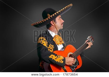 Charro Mariachi playing guitar on black background