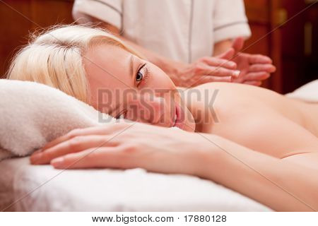 A blond female looking at the camera, receiving a percussive back massage in a spa