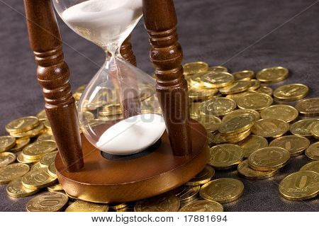 Hourglasses and coin On a grey