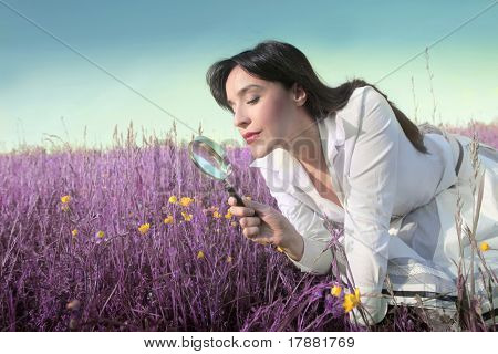Woman observing some flowers through a magnifying glass
