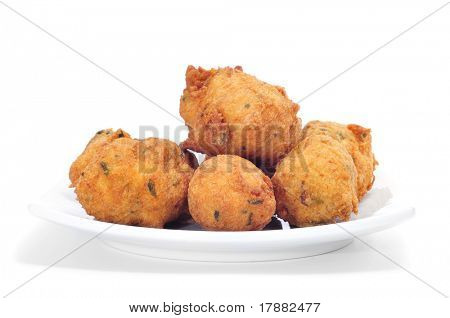 a plate with some cod fritters on a white background