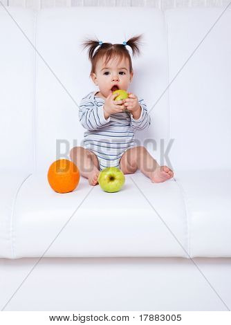 Lovely baby girl sitting on the sofa and eating fruit