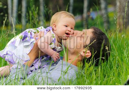 Happy father with daughter resting in the grass
