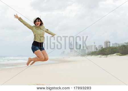 Young Woman Jumps On The Beach With Joyful Screem