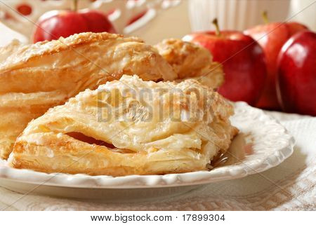 Delicious apple turnovers on decorative plate with fresh gala apples in background.  Closeup with shallow dof.