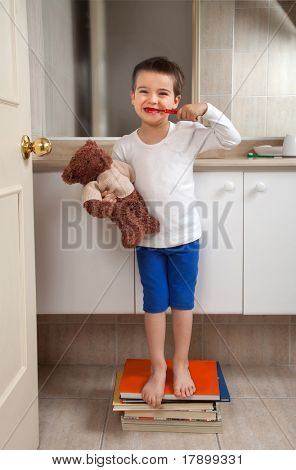 Boy washing teeth with teddy bear standing on some books in a bathroom