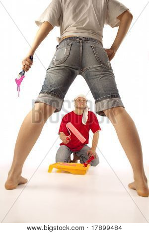 The powerful  forewoman`s legs standing  against  of  young worker with roller
