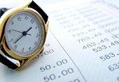 foto of time-saving  - watch resting on finance sheet - JPG