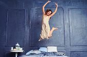 Low angle of a female in the air. Young excited woman jumping on bed. Woman having fun in the bedroo poster