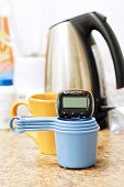 picture of beep  - Tea Timer on measuring cups with coffee pot in background for kitchen concepts - JPG