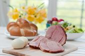 Ham on Easter table with eggs, flowers and decoration