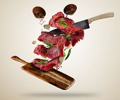 Flying pieces of raw steaks, with ingredients for cooking, served on wooden board. Knife cutting the poster