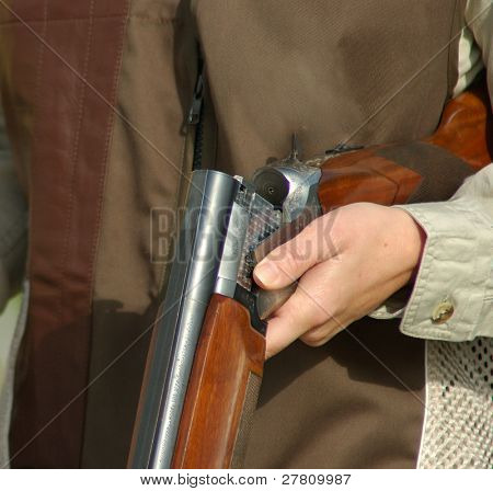 close up of a woman with an open a shotgun