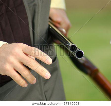 man holding a open shotgun on a trap range