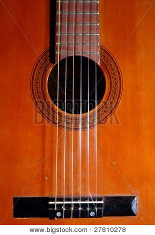Detail of the soundhole, bridge and fret board of a classical guitar