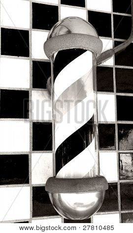 Old fashioned barber poll in black and white on a ceramic tile background