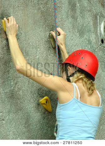 A young woman scaling an artificial rock climbing wall