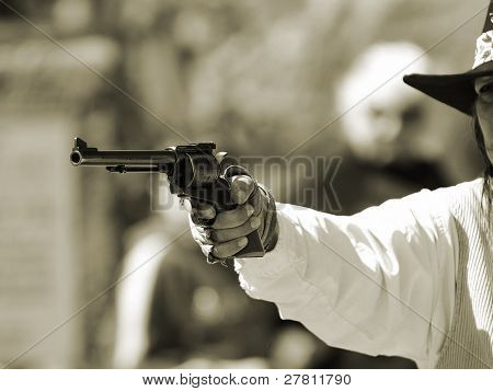 A Calico Gunfighter draws a pistol in the streets of the 1889 Silver boom town of Calico. Located in the Mojave desert.
