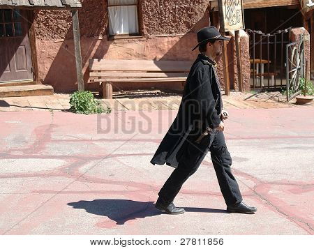 A Calico Gunfighter strolls through the streets of the 1889 Silver boom town of Calico. Located in the Mojave desert.