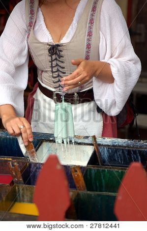 A woman hand dipping candles at the Renaissance Pleasure Faire