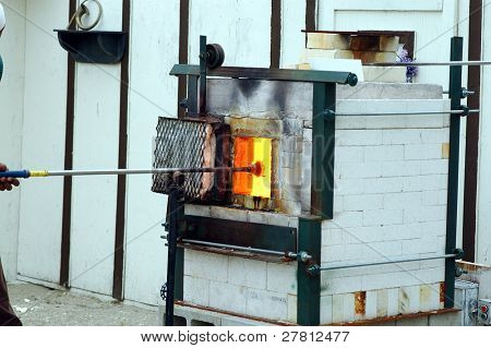 Glass blower heating an orb in the kiln