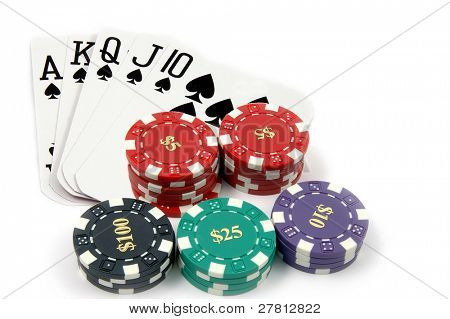 One of the highest hands in poker a Spade Royal Flush with a pile of casino chips isolated on white Card are retired casino cards and the corners have been physically clipped