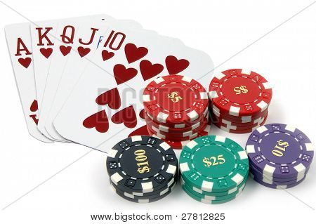 One of the highest hands in poker a Heart Royal Flush with a pile of casino chips isolated on white Card are retired casino cards and the corners have been physically clipped