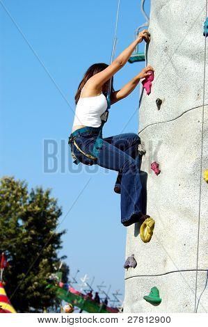 A young woman climbing a rock wall at a County Fair