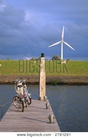 Bicycles And Windmill Above Canal.