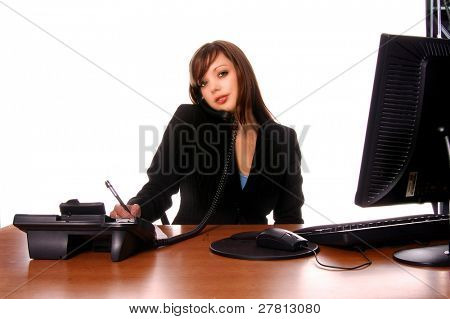 Sexy redheaded business woman in black business suit at her desk and talking on a corded phone  isolated over white