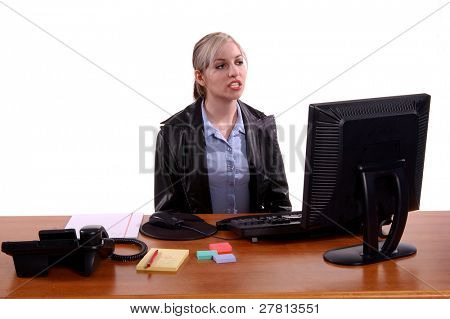 New hire at her desk looking at her computer screen with a unsure look.