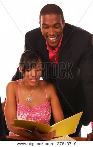 Affluent African American male executive with co-worker going over some files in the office