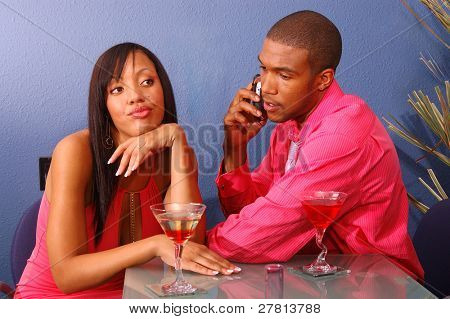 African American couple in a martini bar.Man talking on cell phone while the woman sits by annoyed and bored