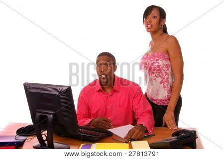 Affluent African American male executive with co-worker surprised while going over some files in the office