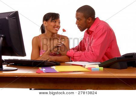 African American  executive brings a flower to his secretary. Perhaps a budding office romance or maybe a show of gratitude on Secretary's Day