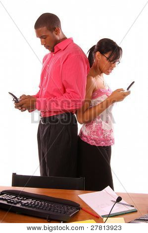 Sexy African American business people using the wireless capabilities of their cell phones to transfer data from one phone to the other