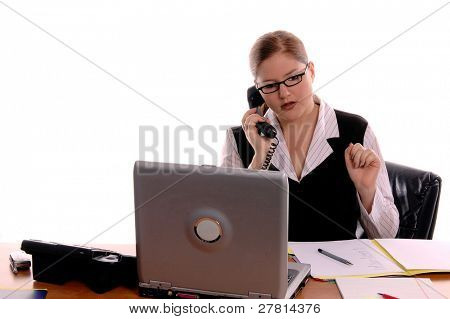 Female office worker with red hair working at her desk and picking up the telephone
